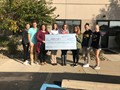 Photo of Coughlin students presenting a check to Candy's Place.