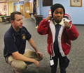 Jeremy Cook watches as Shaheen Richardson tries on new coat provided by WB Firefighters at Heights Murray Elementary. Photo from  Warren Ruda| The Citizens' Voice