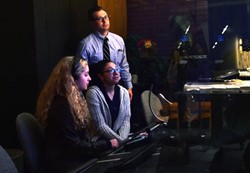 Weiland teaches students Gabby Nichols, 17, and Syndia Perez, 16, how to control the audio during a simulated television broadcast.
